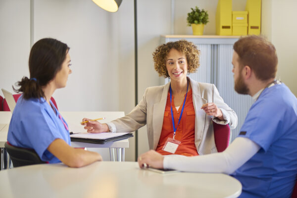 Male and female doctors chat with a female administrator