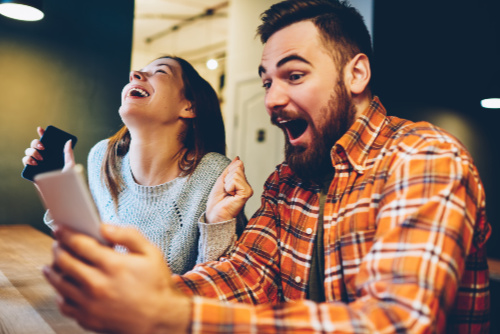 Young man and woman laughing while using their phones