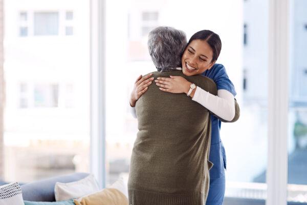 Young nurse hugging a senior woman