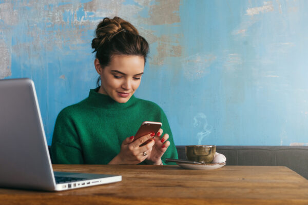 Young woman sitting at table with smartphone and laptop