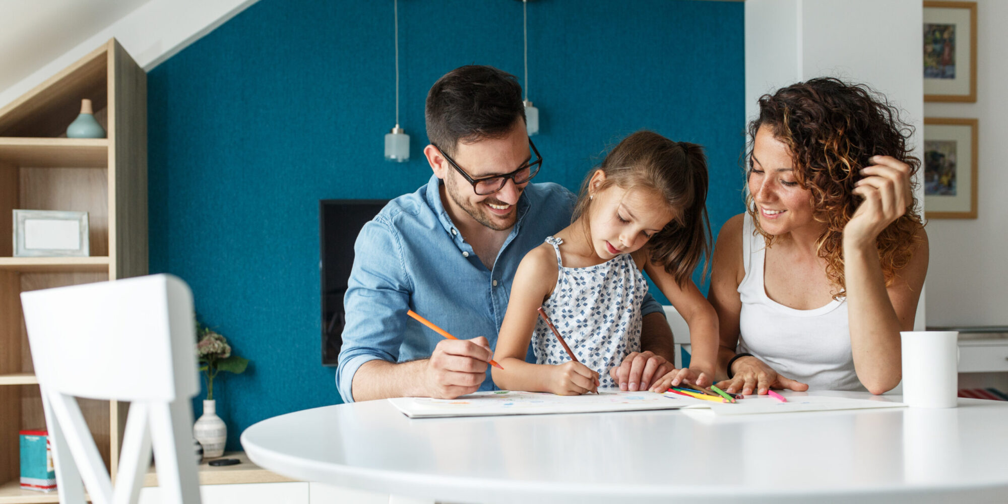Father, mother and daughter drawing together