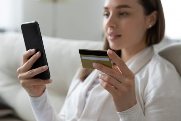 Woman making online payment using credit card and smartphone